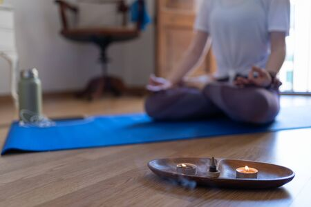 Close-up of incense and candles burning with an unfocused person behind meditating with the mobile phone and the ag Stock Photo
