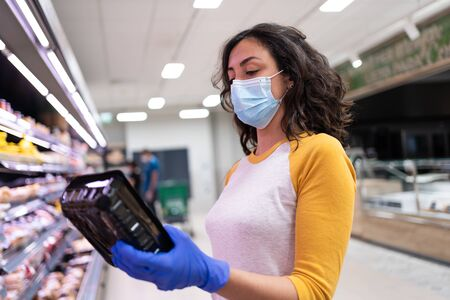 Image of a young woman wearing a mask and gloves buying a packet of fresh pasta in the fresh produce section of a supermarket Stockfoto