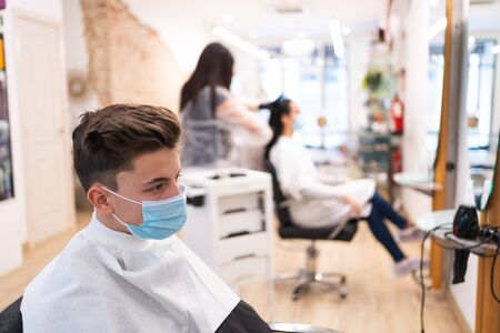 Young boy protected with a mask and keeping a safe distance with another client waiting to have his hair cut at the hairdresser