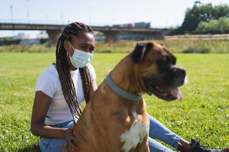 Selective focus on an ethnic african woman wearing a protective mask and sitting next to a boxer dog on the grass with a bridge on the background