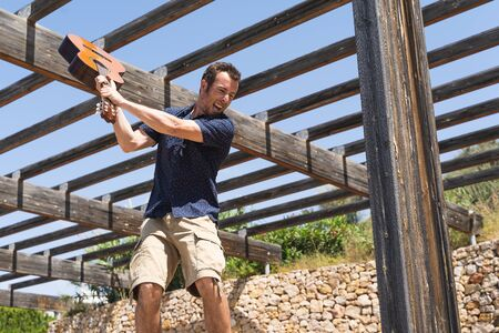 Man with a blue stamped shirt about to break a Spanish guitar with an angry expression under a wooden rail frame Imagens