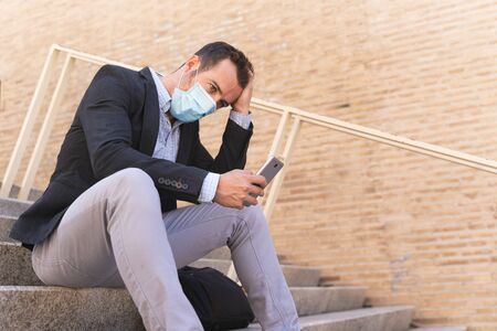 Businessman with a blue jacket and a mask on his face sitting on a staircase in the street with a worried gesture while he touches his head and uses his mobile