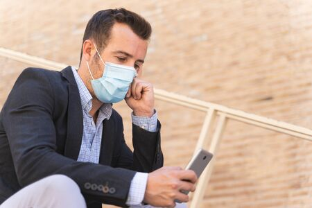 Businessman with a blue jacket and a mask on his face sitting in the street with a thoughtful expression while he touches his face and uses his mobile Foto de archivo