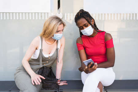Two young women sit on a bench with a wall behind them staring at the mobile phone while wearing a mask on their face to protect themselves