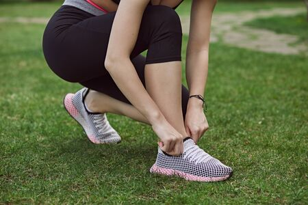 A young woman doing exercises outdoors on green grass. Fitness sporty girl tightening her sneakers