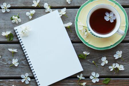 一杯茶和一个满是樱花的空笔记本。空白的地方,你可以放你的文本。