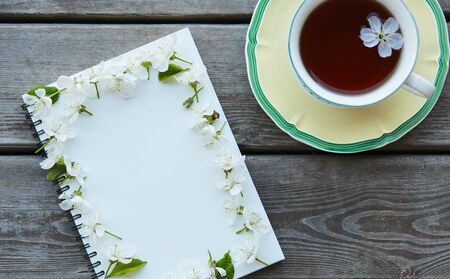 A cup of tea and an empty notebook covered with cherry flowers. Blank space where you can put your text. Archivio Fotografico