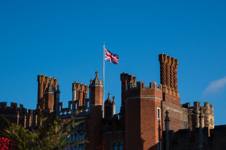 Union Jack flying over Hampton Court Palace in sunshine against blue sky with red currants in the foreground Editorial