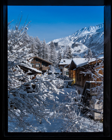 Fresh snowfall covering mountain village and mountain ridge in the Alps seen through a window.