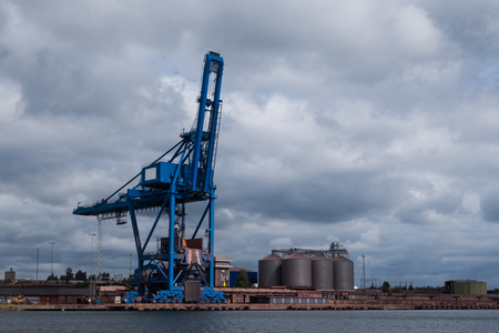 idle: A crane and silos in an industrial harbour by the sea standing idle. Editorial