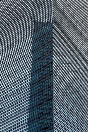 Close-up of modern skyscraper office building facade covered with a lattice of metal beams and bars reflecting neighbouring building Stock Photo