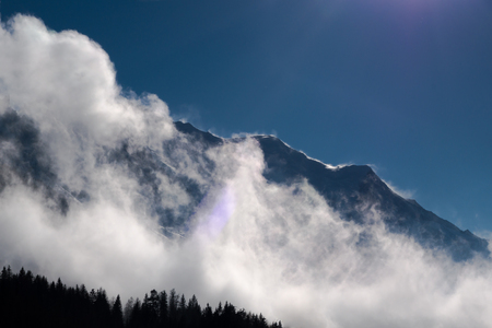 Snow blown off Mont Blanc mountain ridge by strong winds with low cloud cover in glacial valley facing Chamonix
