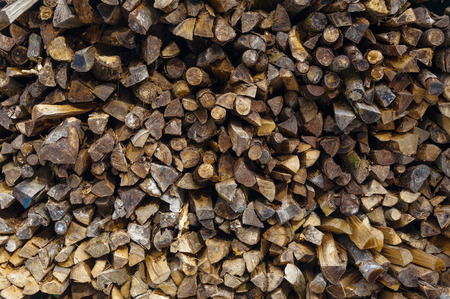 neatly stacked: Firewood cut and stacked neatly in pile outside ready for use in fireplaces and wood burners