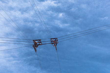 poleas: Cable car ski lift pulley wheels suspended by wires cables high above ground against cloudy sky
