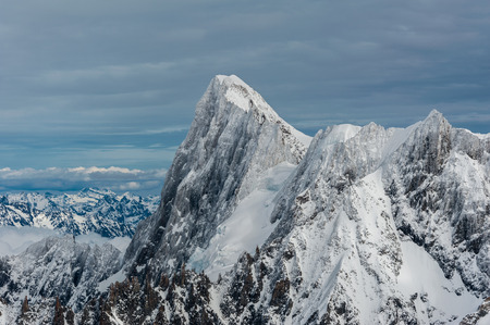 The Grands Jorasses north face covered by recent snow and ice against a clouded sky horizon in winter Stock Photo