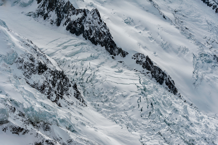 Aerial view of crevasses and seracs of Glacier des Bossons flowing down the side of Mont Blanc in winter