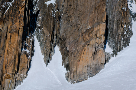 Two climbers scaling a large granite rockface in winter