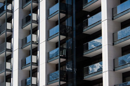 transom: Concrete facade of apartment building with balconies and windows in sunlight. Stock Photo