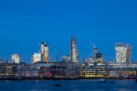 expand: City of London skyline at dusk twilight with landmark skyscrapers office buildings and River Thames against mixed blue and cloud horizon