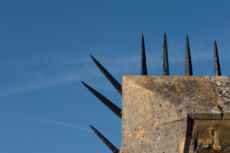 Detail close-up of Tudor era brick wall with a row of sharp black spikes on top edge Stock Photo