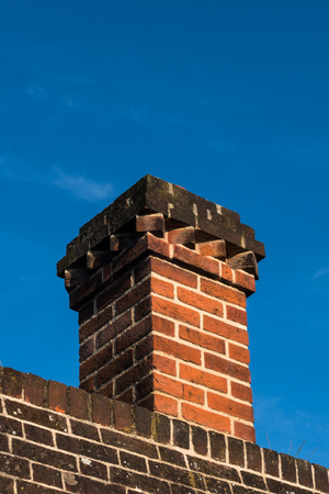 Close-up detail of red brick chimney and chimney pot on exterior wall of Tudor architecture building Stock Photo