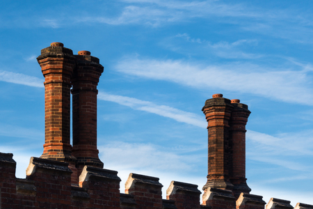 Close-up detail of red brick chimneys and chimney pots on exterior wall of Tudor architecture building Stock Photo