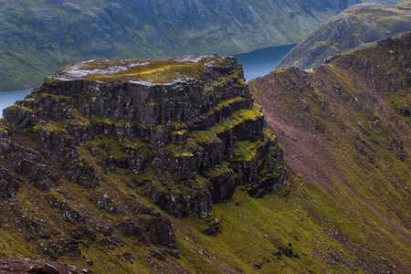 Majestic mountain ridge and plateau below the Munro peak Beinn Tarsuinn in the Fisherfield Forest with rock and heather covered sides Stock Photo