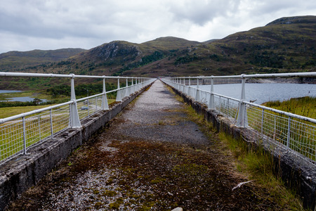 Concrete walkway leading on top of hydroelectric dam wall in Scottish Highlands leading across to overflow point with white metal railings on both sides