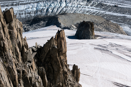 Lone rock climber on top of mountain pinnacle overlooking Glacier du Argentiere in summer Stock Photo