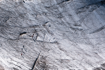 hole: Group of walkers mountaineers secured with ropes crossing between crevasses on Glacier du Argentiere in summer
