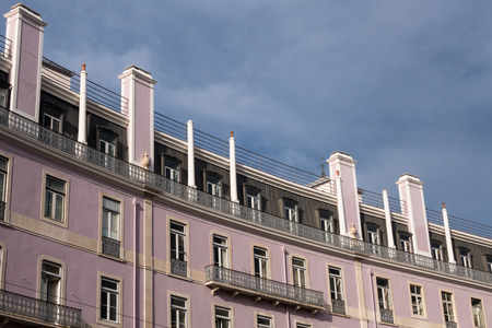 Curving apartment building facade with rows of windows chimneys balconies in sunshine with a cloudy sky behind Stock Photo