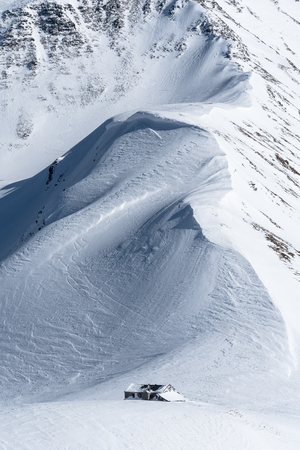 Mountain ridge with large wind packed cornices leaning over partly snow covered alpine mountain hut
