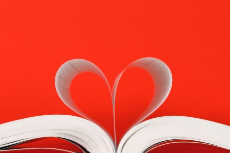 book with pages in heart shape over red background photo