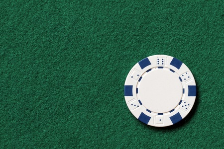 white poker chip on a table with text space photo