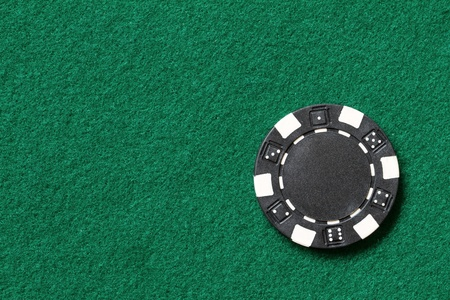 black poker chip on a table photo