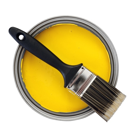 paint container: yellow paint with paint brush over white background Stock Photo