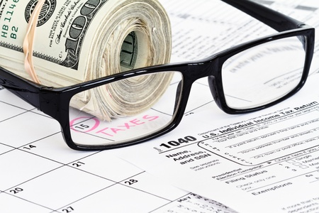 refund money on 1040 tax form with reading glasses