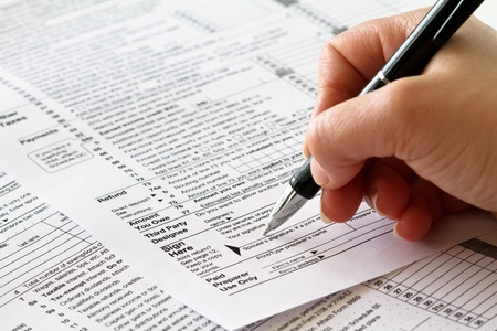 tax return: tax form with hand and pen  Stock Photo