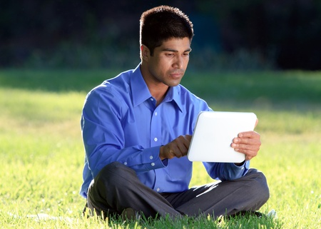 young businessman at the park working with tablet  photo