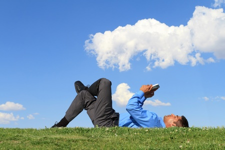 businessman laying down on the grass and working with tablet  photo