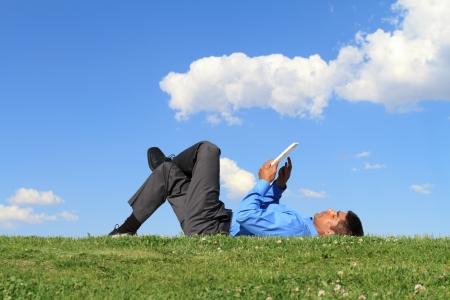 사업가 잔디에 누워 및 정제 작업
