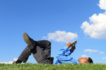 man using computer: businessman laying down on the grass and working with tablet
