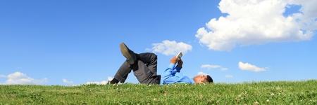 podnikatel, kterým se stanoví na trávě a práci s tabletem