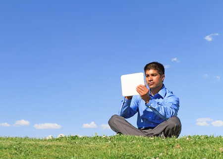 tablet: young businessman at the park working with tablet