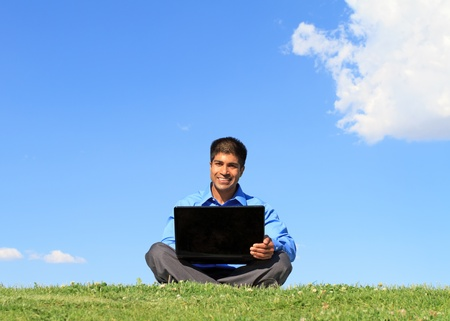 happy businessman with laptop, outdoor against blue sky photo