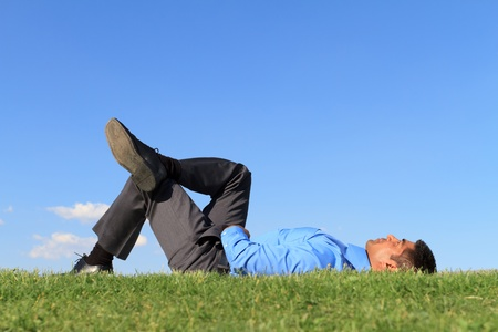 man looking at sky: businessman resting at the park  Stock Photo