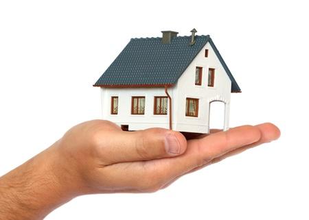 property insurance: casa en miniatura en la mano