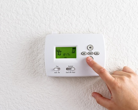 hands in the air: digital thermostat with finger pressing button  Stock Photo