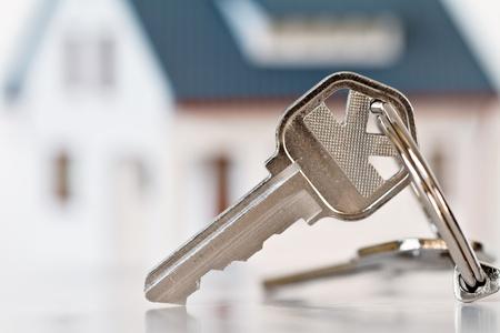 home loans: chiavi con casa su sfondo Archivio Fotografico