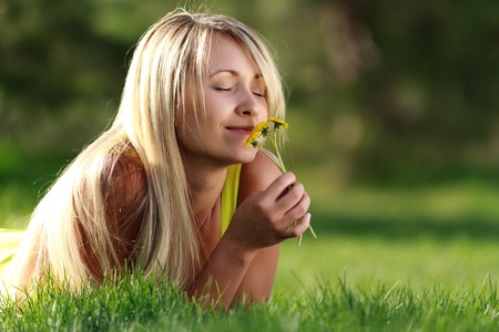 young attractive woman with flowers day dreaming photo